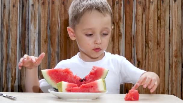 das Kind sitzt am Tisch vor einer Holzwand und isst genüsslich eine Wassermelone.