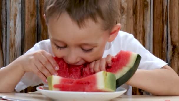 Das Kind beißt ein Stück Wassermelone ab. ein Stück Wassermelone liegt auf einem Teller.