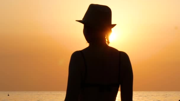 Silhouette of a young woman in a hat on the sea beach, which looks towards the sunset. Fitness, sport, yoga and healthy lifestyle concept