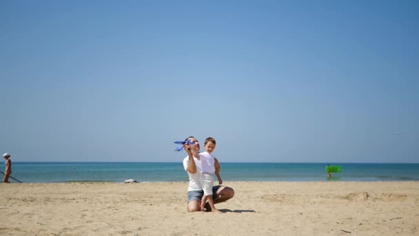 Happy father and son on the sea sandy beach together launch a toy plane. The concept of a happy family, leisure and travel