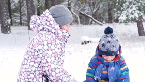Portrait of a happy family: mother and son playing, throwing snow up in a snowy park or forest. Leisure, lifestyle. Emotions of joy and happiness.