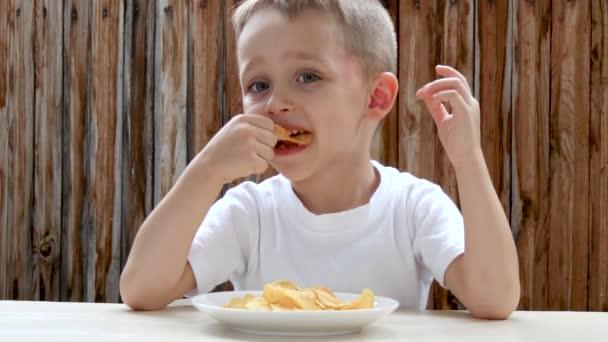 Vor dem Hintergrund einer Holzwand isst ein Kind genüsslich Kartoffelchips. der Junge ist zufrieden mit dem Essen und zeigt den Daumen nach oben.
