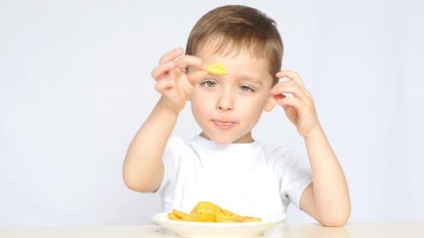 Ein süßer kleiner Junge sitzt am Tisch und isst Chips. Keine gesunde Ernährung für Kinder.