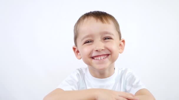 A child of preschool age experiences emotions: happiness, joy, laughter, delight. A little boy on a white background looks into the camera and laughs. Rub.