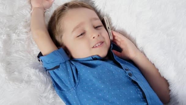 Egy aranyos gyermek feküdt egy fehér kanapén, és beszél a telefonon, tapasztalt őszinte érzelmek: öröm, boldogság, nevetés