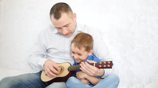 The father holds his little son and teaches him to play the guitar, the cheerful kid claps the guitar as if she plays it. A happy family. Music and parenting.