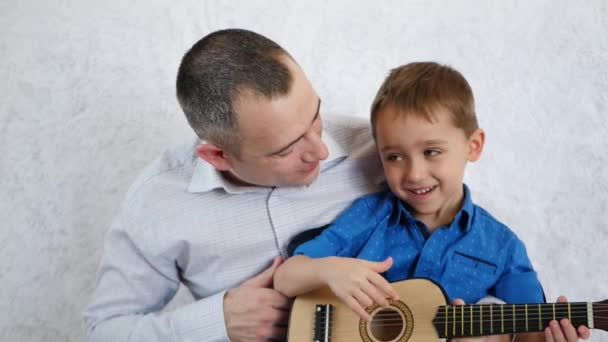 Happy father and son play guitar, sing and laugh