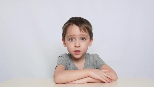 A preschool boy deals with a speech therapist performing arteculation with the tongue. The child sits at the table and looks into the camera.