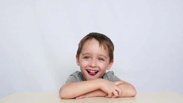 U stolu sedí školní dítě. Chlapec dělá ARTIK s jazykem, směje se a dívá se do kamery. Třídy s terapeutem pro řeč.
