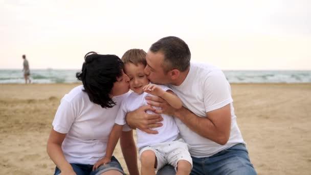 Šťastná Maminka a tatínek líbají své dítě na písčité pláži proti moři s úsměvem v pomalém pohybu