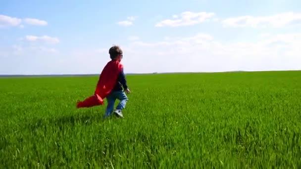 Egy boldog gyerek egy szuperhős jelmez egy piros köpeny, és a maszk fut a zöld fű egy napsütéses napon