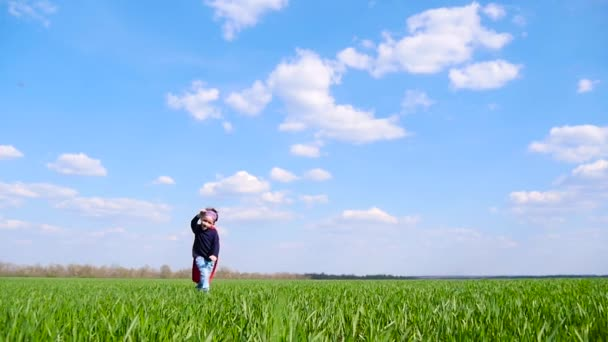A happy child in a superhero costume in a red cloak happily runs across a green field on a sunny day, against a cloudy sky