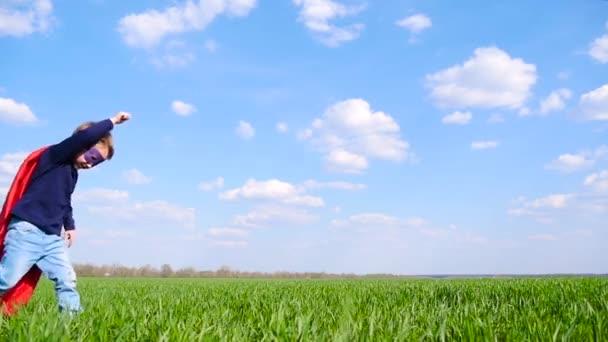 Egy boldog gyermek egy szuperhős jelmez egy piros köpenyt fut át egy zöld mezőben egy napsütéses napon, egy felhős ég