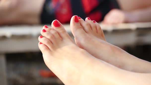 Close-up of the feet of a woman whose toes are painted with red lacquer on the sea coast
