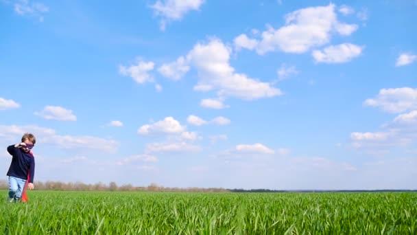 Egy boldog gyermek egy szuperhős jelmez egy piros köpenyt boldogan fut át a zöld mezőben egy napsütéses napon, egy felhős ég