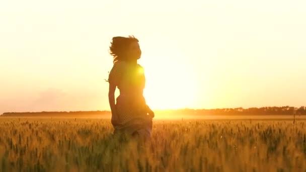 Dívka v šatech mezi zlatými ušima pšenice. Krásná mladá žena běžící při západu slunce.
