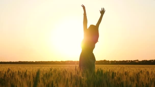 Girl in a dress standing on a wheat field at sunset and spinning, raising his hands up.