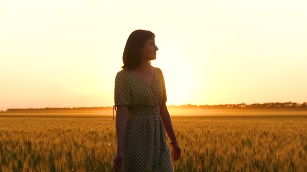 A beautiful girl in a dress is walking on a wheat field during the sunset. Woman touches the hands of wheat ears. Unity with nature, agribusiness, motivation and travel.