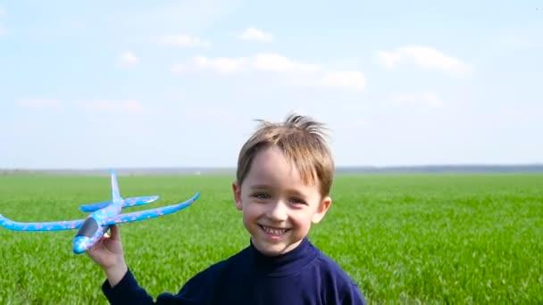 Boldog kisfiú játszó repülőgép futó zöld fű.