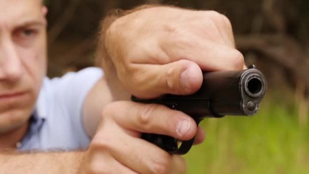 A férfi díjak a fegyvert és a hajtások. Közeli fel a fegyvert, és a Mans arcát a háttérben.