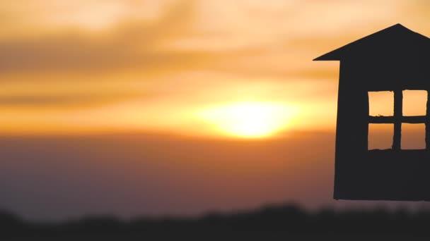 Hände von Männern und Frauen halten ein Modell des Hauses und die Schlüssel gegen den Sonnenuntergang. Silhouette eines Papierhauses.