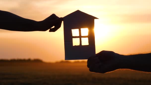 Hands men and women holding a paper house. The silhouette of the house. Happy family, construction and mortgage concept.
