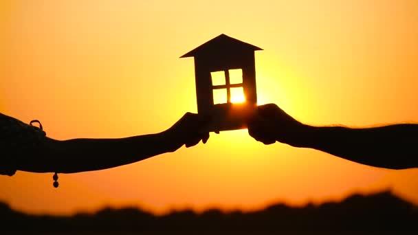 Ein Mann und eine Frau halten ein Papierhäuschen gegen den Sonnenuntergang. die Silhouette des Hauses. das Thema Bauen, Immobiliengeschäfte und Familie.