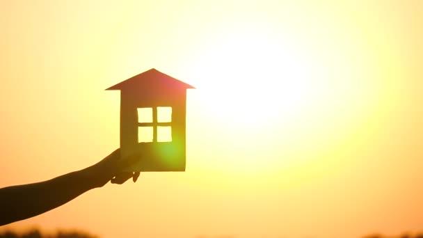 Ženy drží dům před krásným západem slunce. Silueta domu při západu slunce.