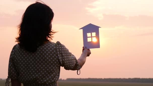 Dívka, která drží papírový dům. Sluneční paprsky procházejí okny papírového domu.