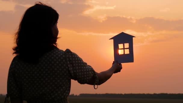 A sziluettje egy lány egy ruhában gazdaságban a Paper House. Gyönyörű naplemente éjjel. Családi boldogság és kényelem.