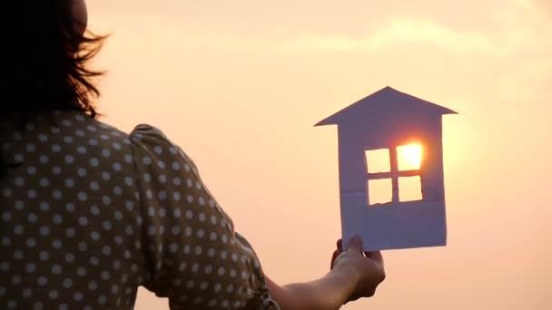 Silhouette eines Papierhauses in Händen bei Sonnenuntergang in der Sonne.