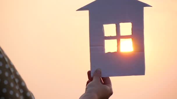 Během západu slunce září v okně papírového domu jasně rudé slunce.