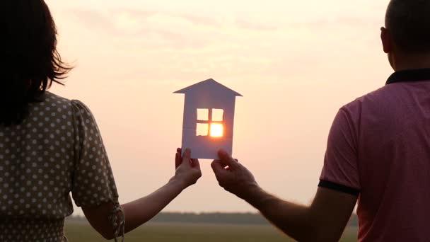 die Silhouette eines Papierhauses in der untergehenden Sonne. Ein Mann und eine Frau halten ein Papierhaus in der Hand und beobachten den Sonnenuntergang. Ein glücklicher Familientraum.