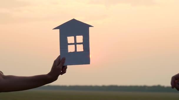 Silueta papírového domu. Ruka ženy prochází po západu slunce vzorem papírového domku v ruce muže. Stavební. Bydlení pro mladou rodinu.