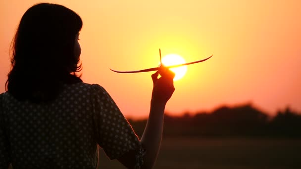 Girl traveler holding a toy plane and imagines flying. Silhouette of a girl at sunset. The concept of tourism, air travel and inspiring people.