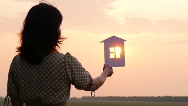 Silhouette eines Mädchens in einem Kleid, das ein Papierhaus gegen den Sonnenuntergang hält. Bau, Immobiliengeschäft.