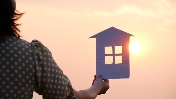 Silueta papírového domu při západu slunce. Sluneční paprsky procházejí okny z papírového domu. Konstrukce, rodinný a realitní koncept.