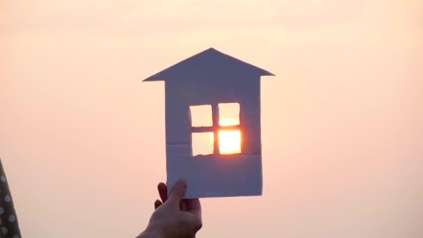 Během západu slunce svítí v okně papírového domu jasně rudé slunce. Silueta papírového domu v ruce.