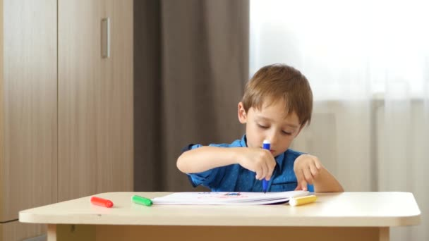 Cute boy sitting at the table and draws bright markers. The child experiences emotions: laughter, happiness, fun. Development and education of preschool children.