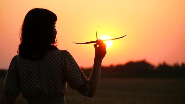Dívka sní o cestování a drží modelový letoun. Silueta šťastné ženy při západu slunce.