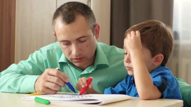 Happy family. Father and child. Dad spends time with his son imagining and painting a picture with colored markers.