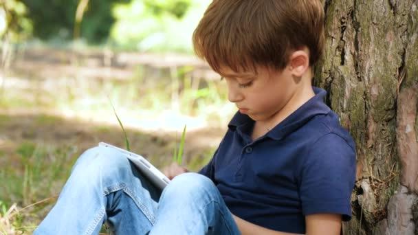 Portrét malého chlapce s tabletem. Šťastné dítě, které si hraje v tabletu na pozadí přírody.