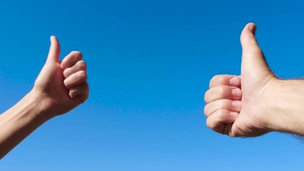 Ruční gesta jsou blízka. Muži a samice ruce proti modrému nebi, OK, dobře, skvěle.
