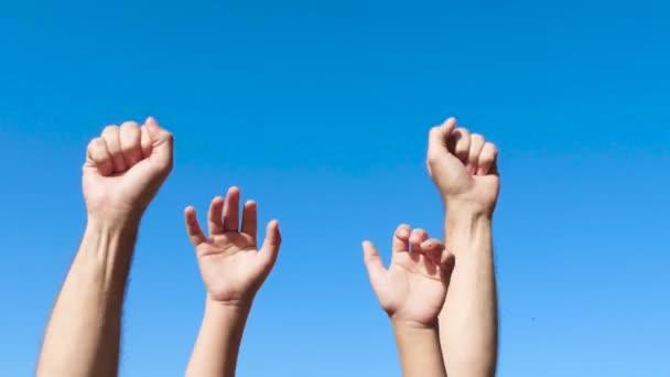 Kezében egy férfi és egy gyerek közelről szemben a kék eget. Két pár kézbilincset és egy viszlát mozdulattal az ujjaikat.
