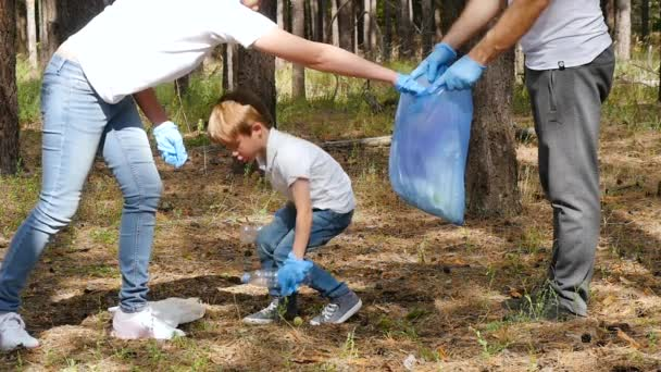 Happy family collects garbage in the forest. Mother and child put garbage in a biodegradable bag. Educate children about environmental protection.
