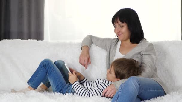 Matka objímá svého syna, když sedí na gauči v pokoji. Malý chlapec hraje tablet. Koncept moderní šťastné rodiny.