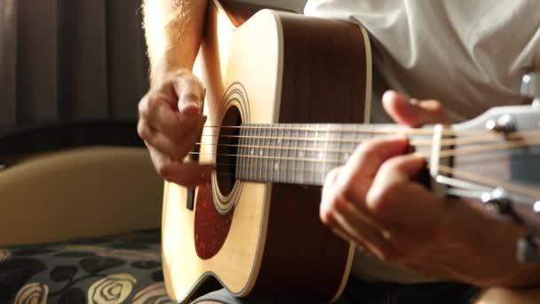 Hudebník hraje rychlý rytmus na žlutou akustickou kytaru. Sluneční paprsky procházejí mezi prsty a strunami.
