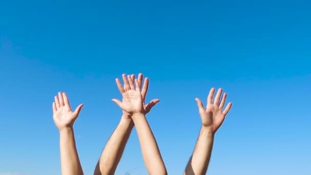 Ruce muže a ženy se houpají na modrém pozadí na bok. Znamení a symboly.