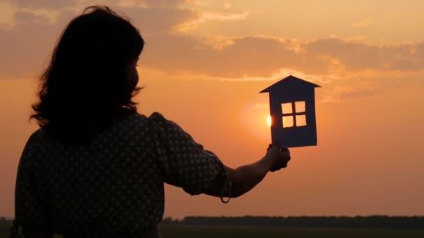 Das Mädchen behält ein Papierhäuschen und träumt von einem großen, gemütlichen Haus und einer glücklichen Familie. Silhouette Papierhäuser bei Sonnenuntergang.
