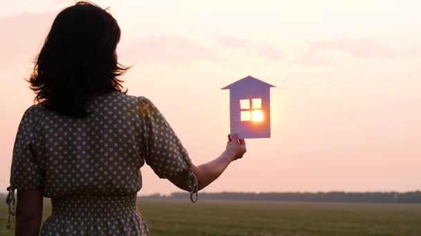 Silhouette of a girl holding a model of a paper house in her hand. The rays of the sun during sunset pass through the window of the paper house. The concept of building a dream of a happy family.